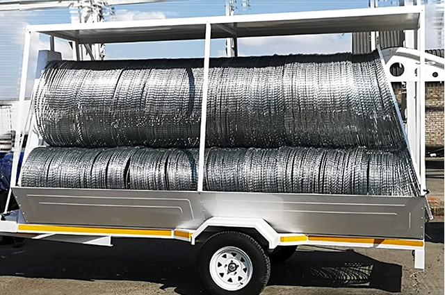 Economy razor wire trailer loaded with barriers side view