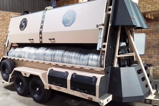 Military razor wire trailer loaded with concertina barriers