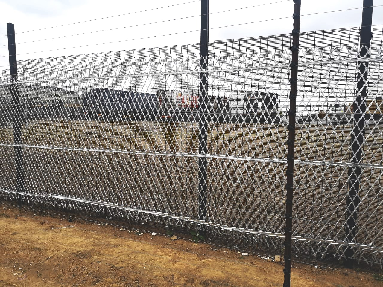 Clear view fencing reinforced with razor mesh spikes and electric fencing topping