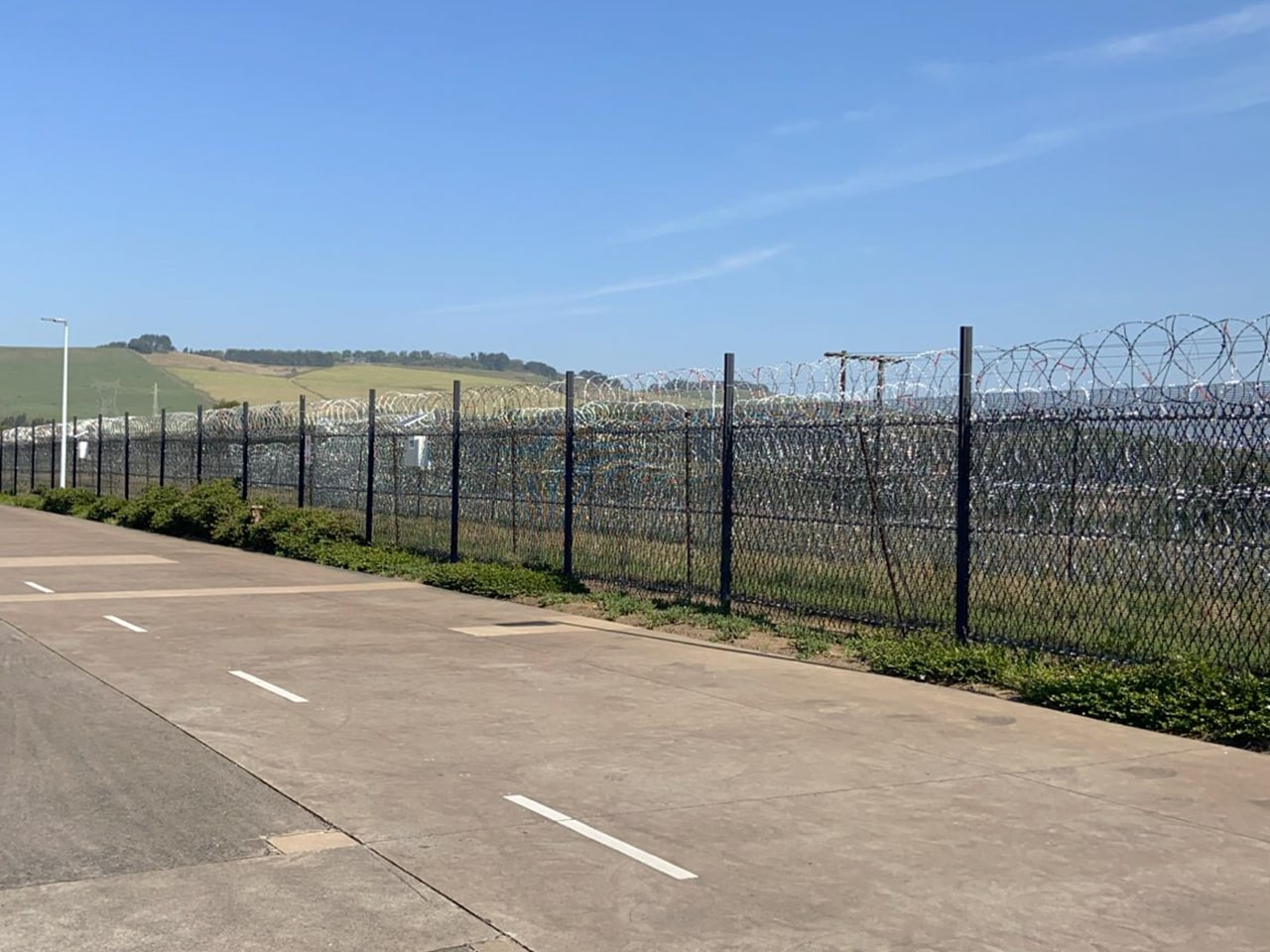 Two layers of perimeter protection razor wire mesh inner and concertina coils outer